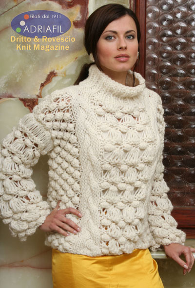 Free knitting pattern for a ladies sweater in chunky yarn with cable and bobble stitch details and a turtleneck.