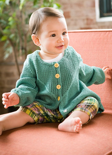 Baby cardigan featuring U-shaped plackets with ribbed stitches framed by graceful cables