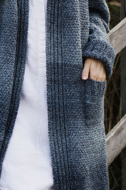 Free Knitting Pattern. This long ladies cardigan with pockets is knitted in a combination of mock fisherman's rib and broken seed stitch.
