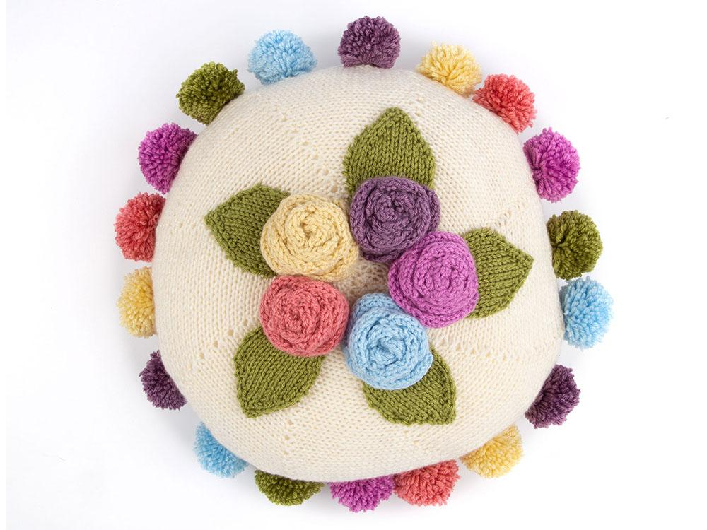Free Knitting Pattern for a Pearl Round Floral Cushion. Round cushion with knit roses and pom poms.