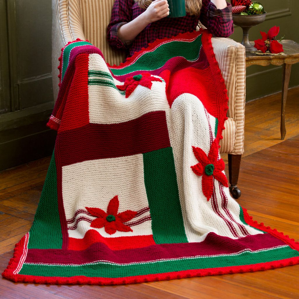 Free christmas knitting pattern for a throw with poinsettia motif